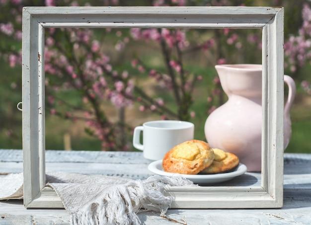 Moldura branca, jarro de porcelana rosa, xícara e confeitaria em uma mesa de quadros brancos contra o fundo de um arbusto florido