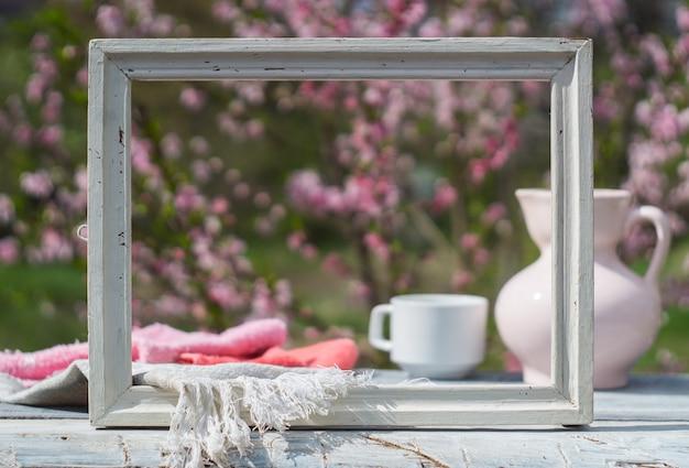 Moldura branca, jarro de porcelana rosa, xícara e guardanapo em uma mesa de quadros brancos contra o fundo de um arbusto florido