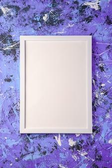 Moldura branca modelo vazio na superfície azul e roxa texturizada, vista superior, espaço de cópia de maquete