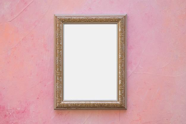 Moldura branca ornamentada dourada na parede rosa
