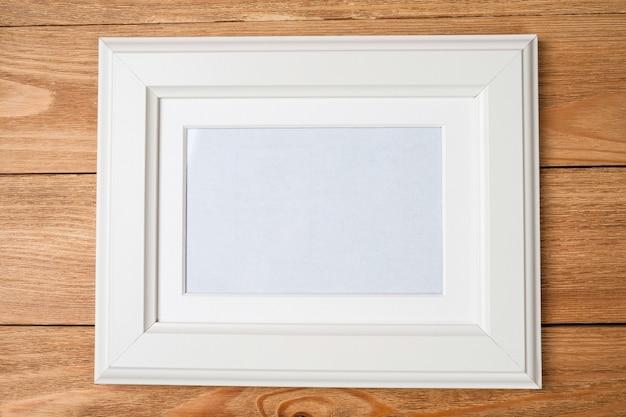 Moldura branca para fotos na parede de madeira