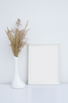 Moldura branca para fotos no interior branco com vaso e grama dos pampas
