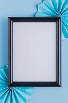 Moldura branca vazia e origami ventilador sobre o pano de fundo azul