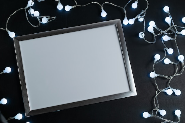 Moldura branca vazia em um quadro negro com luzes brilhantes led