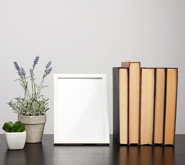 Moldura branca vazia, pilha de livros e um pote de lavanda crescente