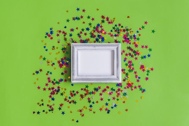 Moldura cinza com confetti em um fundo verde