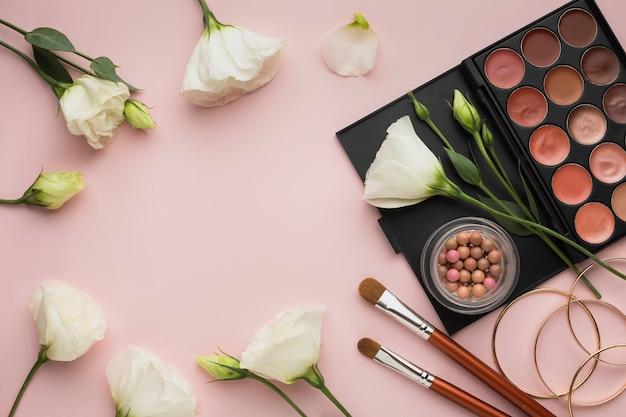 Moldura circular de vista superior com flores e paleta de beleza
