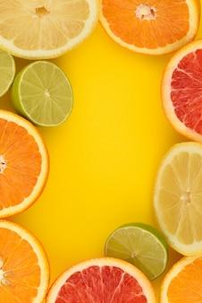 Moldura cítrica. as frutas cítricas misturam a configuração plana, incluindo limão, limão, toranja e laranja em um fundo amarelo.
