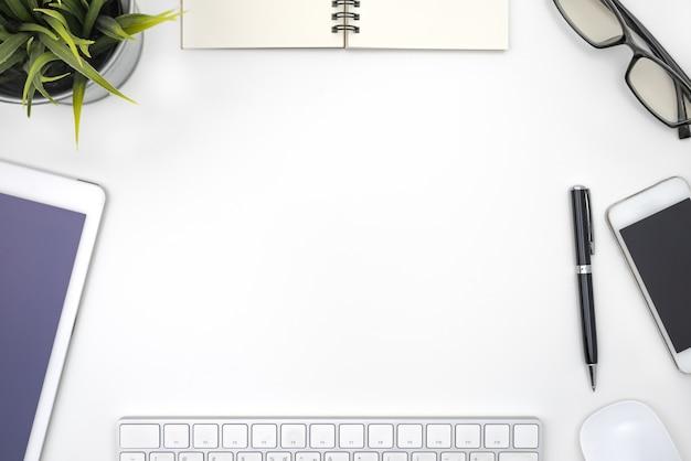 Moldura com equipamento de escritório na mesa branca