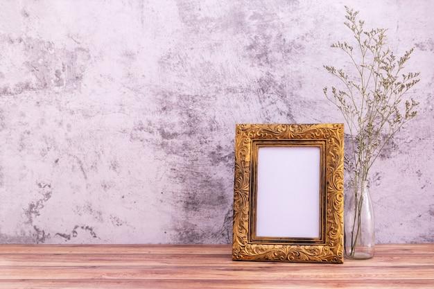 Moldura com flores na parede e mesa de madeira