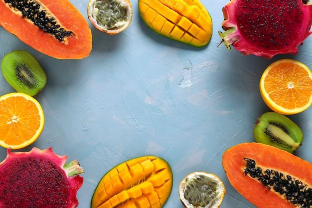Moldura com metades de frutas tropicais: mamão, manga, dragão, kiwi, laranja e maracujá em uma superfície azul clara, vista de cima, espaço para texto