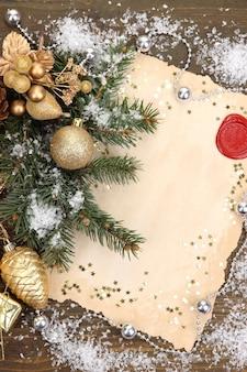 Moldura com papel vintage e decorações de natal na mesa de madeira