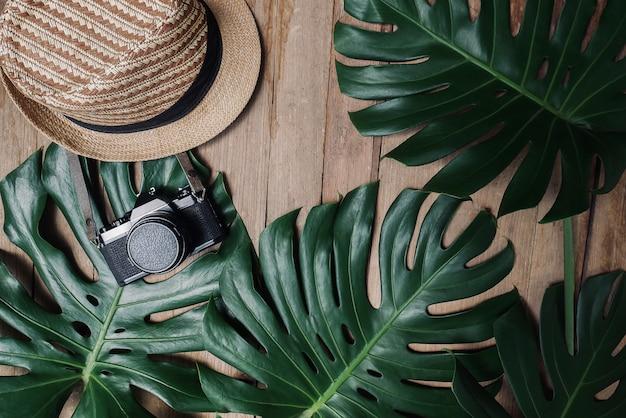 Moldura criativa plana leiga da natureza tropical deixa monstera em fundo rústico de madeira grunge com câmera retro e chapéu