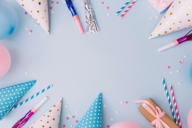 Moldura de aniversário feita de balões; soprador de chifres de festa; chapéu de festa e granulado em fundo azul