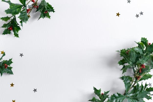 Moldura de canto festiva de natal decorada com folhas verdes de azevinho e confetes de estrelas em branco b