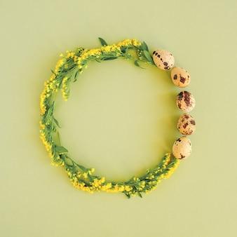 Moldura de círculo festivo de feliz páscoa. layout de páscoa feito de ovos de codorna e flores amarelas sobre fundo verde, com espaço de cópia