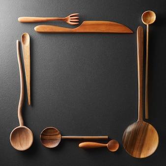 Moldura de colheres de madeira, garfos e uma faca em fundo preto