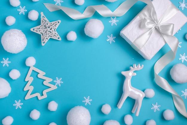 Moldura de composição de natal / ano novo com objetos brancos: bolas, relógio, veado, caixa de presente e decoração. padrão de natal com neve em um fundo azul