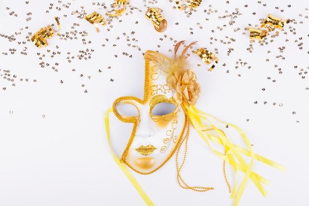 Moldura de confete dourado e máscara de ouro