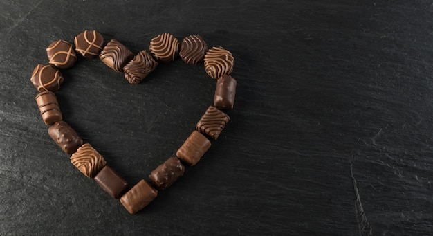 Moldura de coração de chocolate feita com vários tipos de bombons