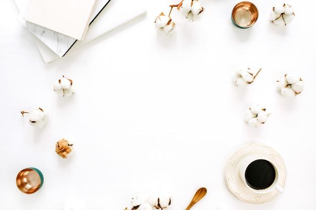 Moldura de cotonetes, xícara de café, pratos dourados, caderno na superfície branca