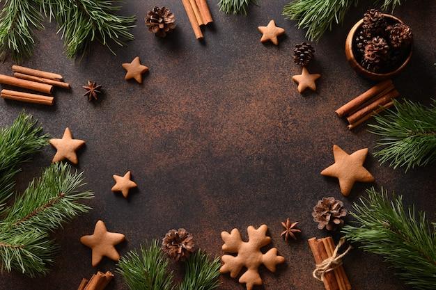 Moldura de cozimento de natal com biscoitos artesanais de gengibre em fundo marrom. comida tradicional de férias. estilo liso leigo. vista de cima. copie o espaço.