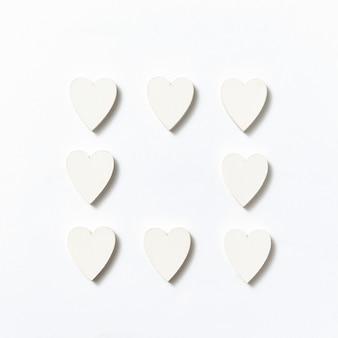 Moldura de decoração festiva feita de corações de papel feitos à mão em uma parede cinza clara com sombras suaves, copie o espaço. vista superior do dia dos namorados.