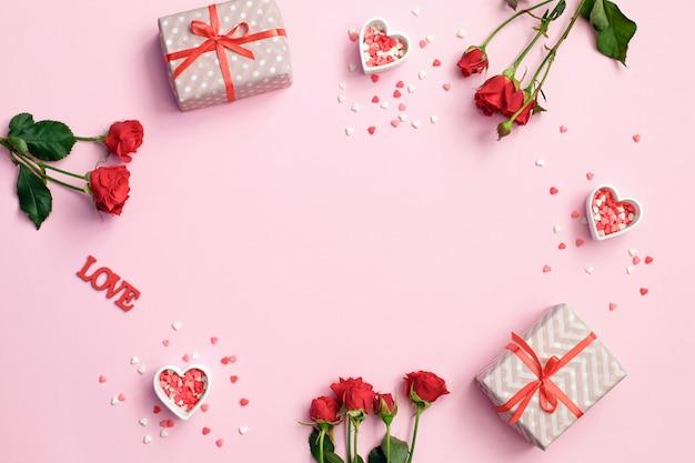 Moldura de dia dos namorados feita de flores rosas, presentes corações no fundo rosa