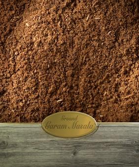 Moldura de especiarias garam masala moída em madeira com etiqueta dourada