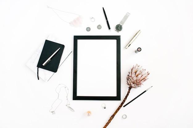 Moldura de foto com tela em branco, relógio de caderno de flor protea e acessórios femininos em fundo branco vista plana de cima mesa de escritório