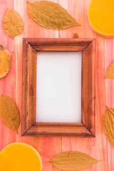 Moldura de foto entre folhagem seca e frutas
