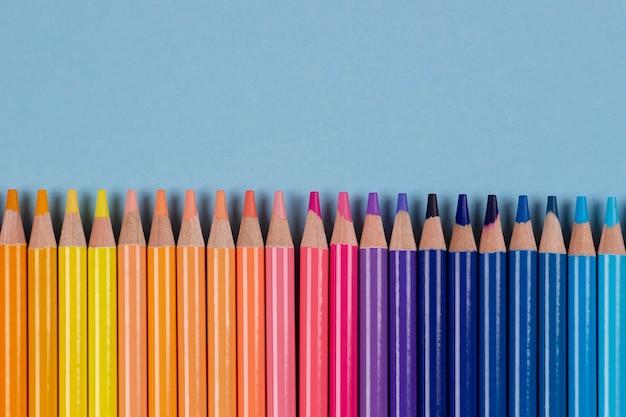 Moldura de lápis de cor em fundo azul claro vista de cima aprendizagem diversidade de arte criativos entretenimentos ...