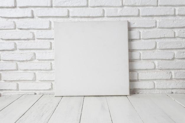 Moldura de lona branca vazia em uma mesa de madeira