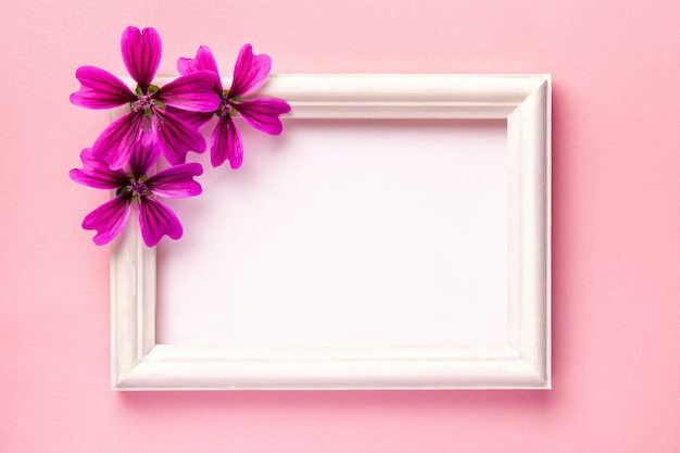 Moldura de madeira branca com flores roxas em fundo de papel rosa.