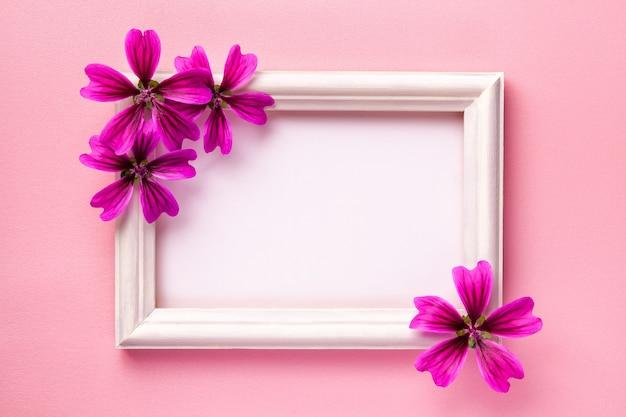 Moldura de madeira branca com flores roxas