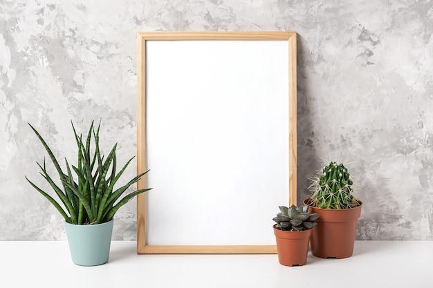 Moldura de madeira com cartão branco em branco e flores verdes de plantas de casa em um vaso na mesa na parede de concreto cinza