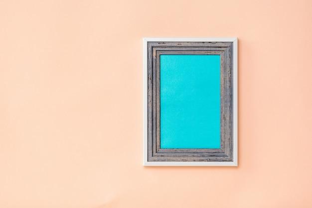 Moldura de madeira com fundo azul dentro da cama em fundo coral. a tendência de cores. minimalismo. plano de fundo para colocação de fotos.