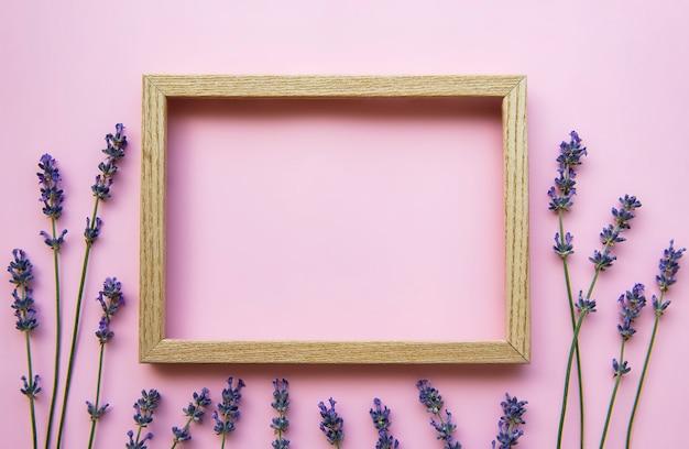 Moldura de madeira com lindas flores de lavanda perfumada na superfície rosa