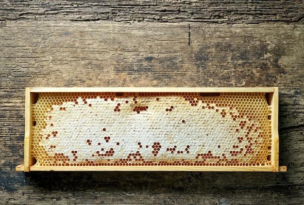 Moldura de madeira de favos de mel na mesa da cozinha rústica, vista superior