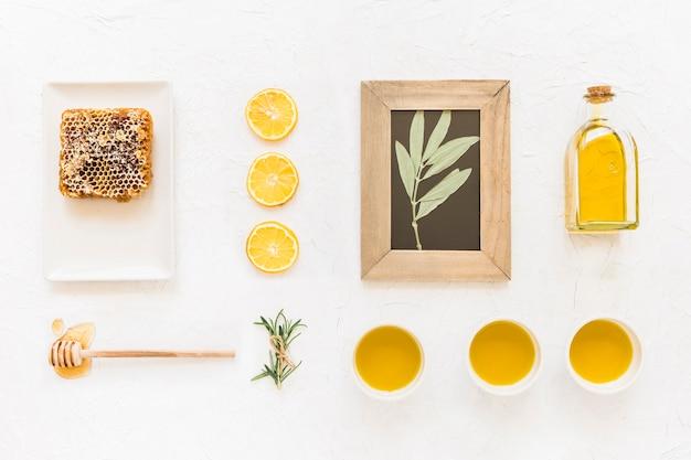 Moldura de madeira de galho com ingredientes de óleo e favo de mel