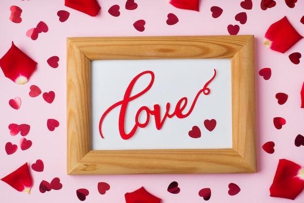 Moldura de madeira e a palavra amor, pétalas de rosas e corações vermelhos.