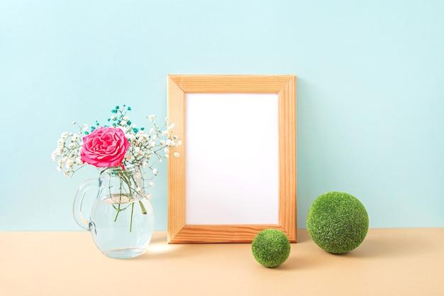 Moldura de madeira e buquê de flores em um vaso de vidro em fundo pastel. flores de gipsófila e rosa rosa na prateleira ou mesa. zombe com elementos de decoração. copie o espaço.