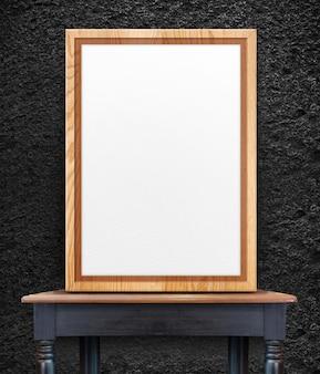 Moldura de madeira em branco encostado na parede de pedra preta na mesa de madeira vintage