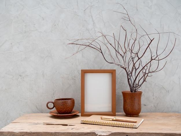 Moldura de madeira em branco simulada copo de café marrom caderno e coral em vaso de coco na mesa de madeira de teca com espaço de superfície de parede de concreto para produtos