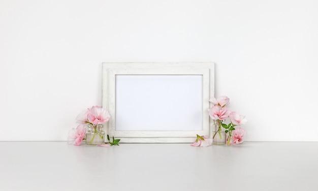 Moldura de madeira horizontal, garrafinhas com flores cor de rosa