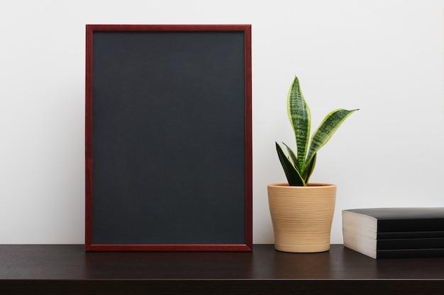 Moldura de madeira marrom ou maquete de quadro-negro na orientação de retrato com um cacto em uma panela e um livro na mesa de trabalho escura e fundo branco