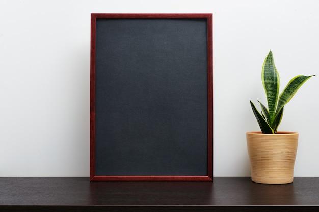 Moldura de madeira marrom ou maquete de quadro-negro na orientação de retrato com um cacto em uma panela na mesa de trabalho escura e fundo branco
