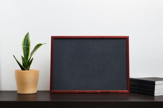 Moldura de madeira marrom ou maquete de quadro-negro na orientação paisagem com um cacto em uma panela e um livro na mesa escura da área de trabalho e fundo branco