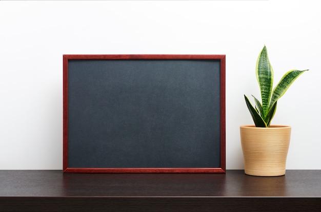 Moldura de madeira marrom ou maquete de quadro-negro na orientação paisagem com um cacto em uma panela na mesa de trabalho escura e fundo branco