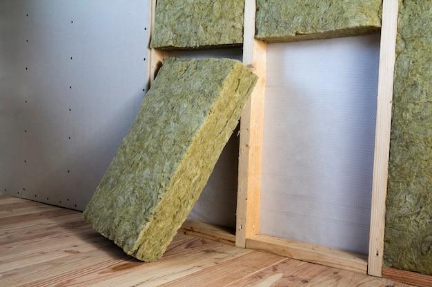 Moldura de madeira para futuras paredes com placas de drywall isoladas com lã de rocha e pessoal de isolamento de fibra de vidro para barreira contra o frio. conceito de casa, economia, construção e renovação confortável e acolhedor.